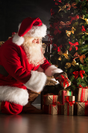 Santa putting gifts under Christmas tree in dark room 写真素材