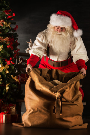 Santa Claus opening his sack and taking gifts under Christmas tree at night at living room at childrens home photo