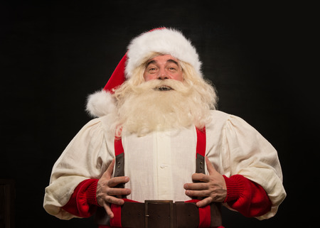 santa suit: Santa Claus laughing loudly against dark background