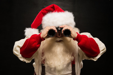 discover: Santa Claus with binoculars against dark background Stock Photo