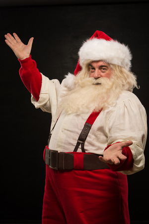 Santa Claus portrait expressing gesturing and presenting something against dark background photo