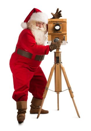 viejito pascuero: Pap� Noel toma el cuadro con la c�mara de madera vieja. Retrato de cuerpo entero aisladas sobre fondo blanco