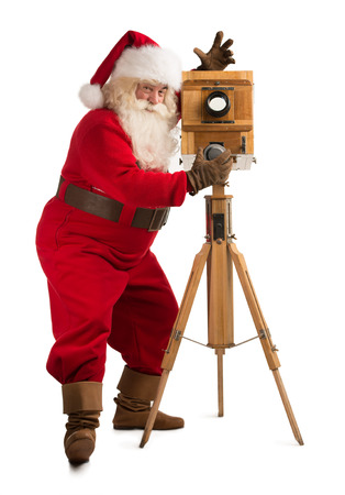 looking at camera: Santa Claus taking picture with old wooden camera. Full length portrait isolated on white background