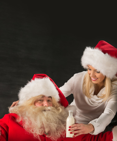 taking a wife: Happy Santa Claus taking milk in glass bottle from his wife at home. Lots of copyspace Stock Photo