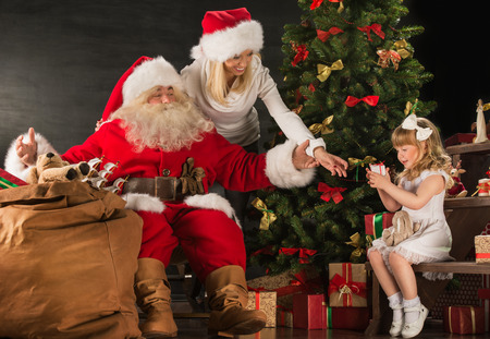 Photo of cute girl and her mother and Santa Claus at home near Christmas tree photo