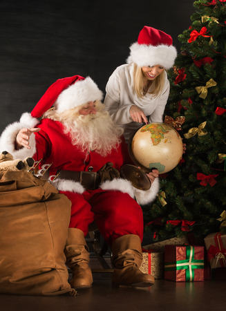 Santa Claus and his wife or helper holding globus and discussing their route to children or choosing vacation destination at home photo