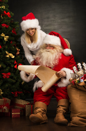 Portrait of happy Santa Claus sitting at his room at home with his woman helper near Christmas tree and big sack and reading Christmas letter or wish list photo