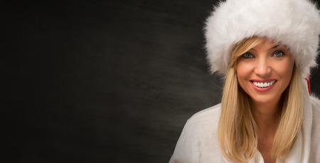 Beautiful adult woman wearing Santa Claus hat closeup face portrait photo