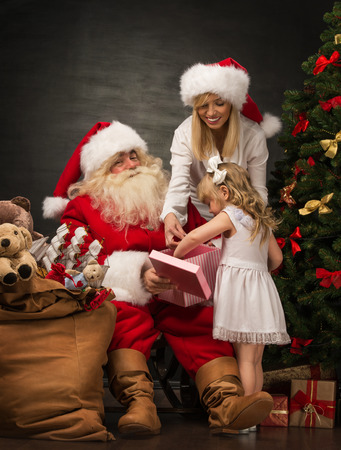 Photo of cute girl and her mother and Santa Claus holding giftbox and opening it at home near Christmas tree