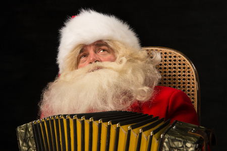 Santa Claus sitting in armchair at home and playing music on accordion. Christmas party merriment photo