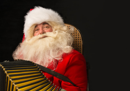 Santa Claus sitting in armchair at home and playing music on accordion. Christmas party merriment. Lots of copyspace photo