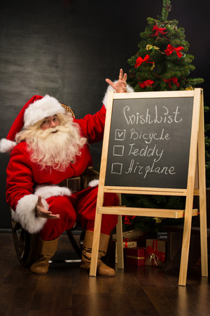 wishlist: Santa Claus sitting near chalkboard with wishlist sign and blank copy space for checkboxes and your text
