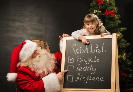 elf: Santa Claus with child sitting near chalkboard with wish list and checking it Stock Photo