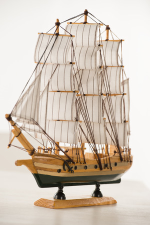 Wooden ship toy model on white table against white background photo