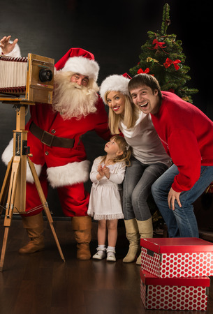Santa Claus taking picture of full family with old wooden camera at home near Christmas tree. Capturing moments of happiness