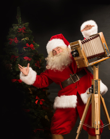 Santa Claus taking picture with old wooden camera standing near Christmas tree at home  photo