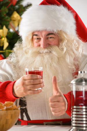 Portrait of happy Santa Claus at home looking at camera and thumbs up while eating cookies and drinking tea photo