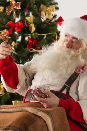 Astonished Santa Claus measuring his temperature with thermometer, feeling ill. Christmas in Danger! photo