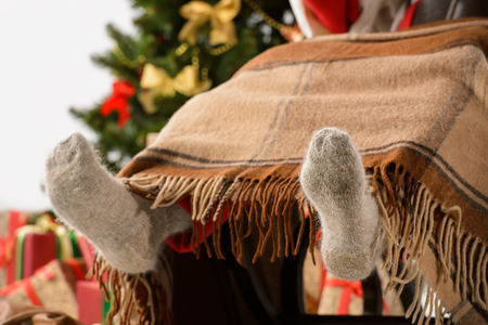 Santa sitting in rocking chair near christmas tree and warming his feet near fireplace. Closeup of Santas feet in wool socks photo