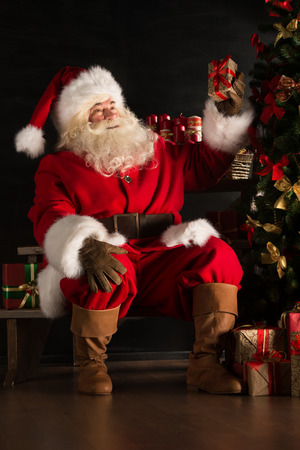 Santa placing gifts under Christmas tree in dark room photo