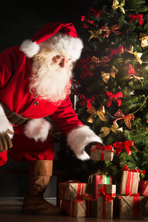 Santa putting gifts under Christmas tree in dark room Stock Photo
