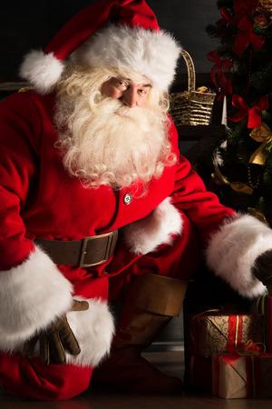 Santa plaatsen cadeautjes onder de kerstboom in de donkere kamer