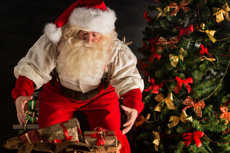 carefully: Santa Claus opening his sack and taking gifts under Christmas tree at night at living room at childrens home
