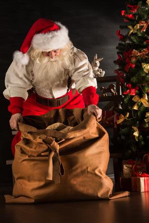 santa claus: Santa Claus opening his sack and taking gifts under Christmas tree at night at living room at childrens home