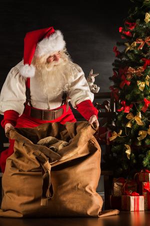 viejito pascuero: Santa Claus abriendo su saco y aceptar regalos bajo el �rbol de Navidad por la noche en la sala de estar en casa de los ni�os Foto de archivo