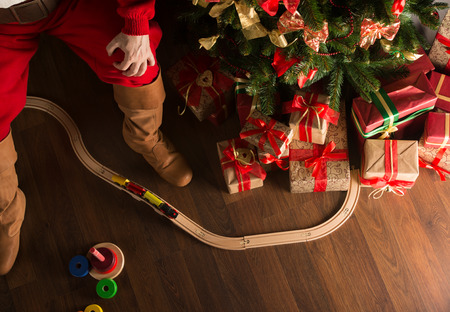 Unrecognizable Santa Claus playing with wooden railroad near Christmas tree. Top view indoors at dark room photo