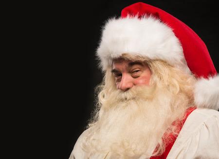 Kerstman vintage stijl portret lachend tegen de donkere zwarte achtergrond Stockfoto