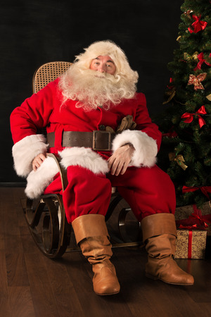 Santa Claus sitting in a comfortable rocking chair near the Christmas tree at home photo