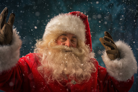 Santa Claus making magic at night under snow outdoors photo