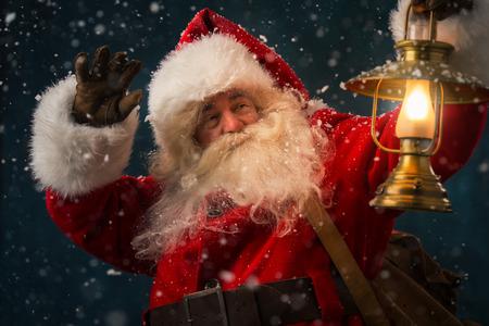 Portret van de gelukkige Kerstman die zak met cadeaus en wandelen onder sneeuwval met vintage lantaarn buitenshuis Stockfoto