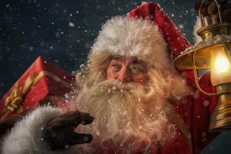 Porträt von glücklich Weihnachtsmann, Sack mit Geschenken und zu Fuß unter Schneefall mit Vintage Laterne im Freien Standard-Bild - 31532161
