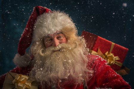 Photo of happy Santa Claus outdoors under snowfall carrying gifts to children