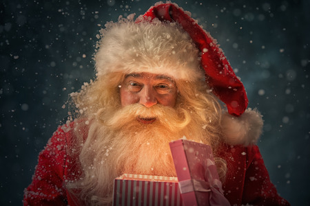 Photo of kind Santa Claus opening and giving xmas present to camera under snowfall