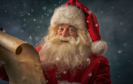 Portrait of happy Santa Claus reading Christmas letter outdoors at north pole under snowfall