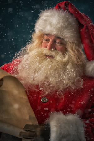 Portrait der glücklichen Weihnachtsmann liest Weihnachtsbrief im Freien am Nordpol unter Schneefall Standard-Bild - 31532176