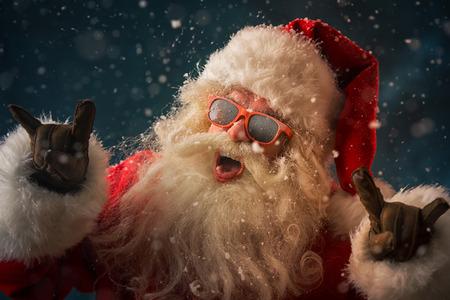 Kerstman draagt een zonnebril dansen buiten op Noordpool in sneeuwval. Hij viert kerst na hard werken Stockfoto