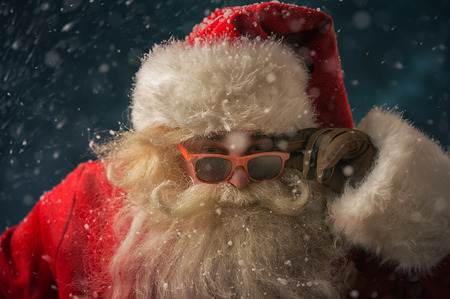 sunglasses: Santa Claus wearing sunglasses dancing outdoors at North Pole in snowfall. He is celebrating Christmas after hard work