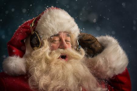 cantando: Santa Claus está escuchando música en los auriculares con gafas de sol. Navidad. Foto de archivo