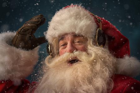 Santa Claus is listening to music in headphones wearing sunglasses. Christmas. photo