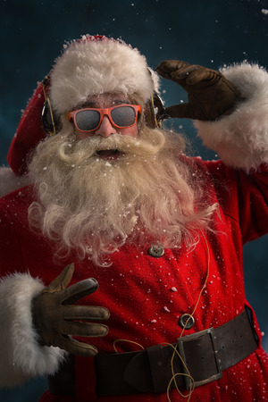Santa Claus is listening to music in headphones wearing sunglasses. Christmas. photo