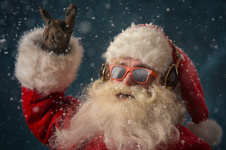 Santa Claus is listening to music in headphones wearing sunglasses. Christmas. Stock Photo