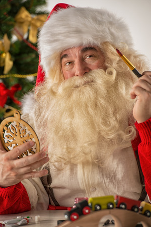 Santa Claus in his workshop making new toys for Christmas Presents for children around the world photo
