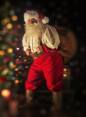 Portrait of Santa Claus carrying huge sack with presents indoor at home near Christmas tree photo