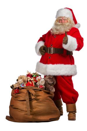 Real Santa Claus duimen omhoog in de buurt van grote zak vol geschenken, geïsoleerd op een witte achtergrond. Volledige lengte portret