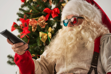 holiday movies: Santa Claus sitting in rocking chair near Christmas Tree at home and watching tv or home theater wearing 3d glasses and holding remote control