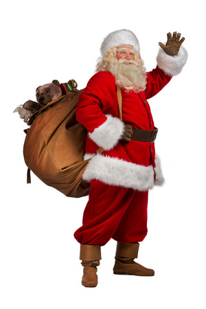 Real Santa Claus carrying big bag full of gifts, isolated on white background. Full length portrait